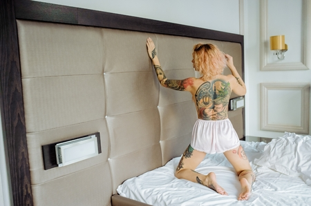 Beautiful bride with tattoo in lingerie showing sexy pose standing at bed over her bedroom. Color. Sexual memories. Pictures on spin.
