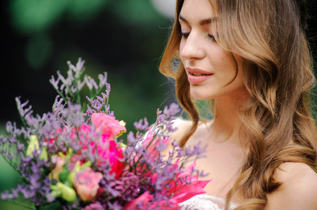 elegant staircase: Outdoor summer closeup portrait of young pretty cute girl with flouwers on her hands. Beautiful bride posing at outdoor. Woman in rose wedding dess standing near in park. Photo has gorgeus model. Stock Photo