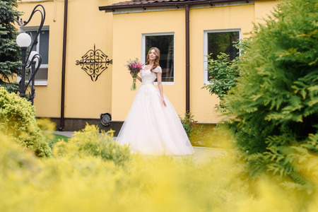 gorgeus: Outdoor summer portrait of young pretty cute girl with flouwers on her hands. Beautiful bride posing at outdoor. Woman in rose wedding dess standing in park near old building. Photo has gorgeus model. Stock Photo
