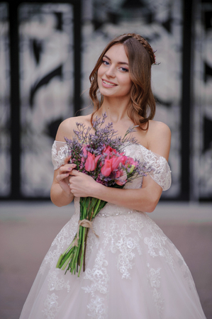 elegant staircase: Outdoor summer closeup portrait of young pretty cute girl with flouwers on her hands. Beautiful bride posing at outdoor. Woman in rose wedding dess standing near old building. Photo has gorgeus model. Stock Photo