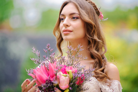 gorgeus: Outdoor summer closeup portrait of young pretty cute girl with flouwers on her hands. Beautiful bride posing at outdoor. Woman in rose wedding dess standing near old building. Photo has gorgeus model. Stock Photo