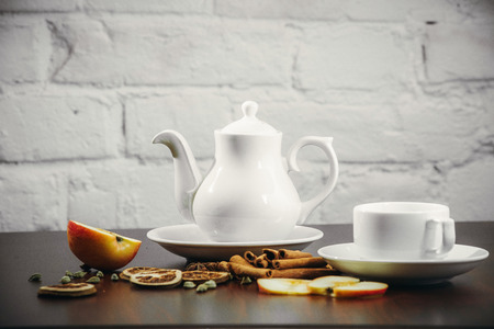 fireclay: Tea cups with teapot on old wooden table. Fruit ginger hot drink. White background. Stock Photo