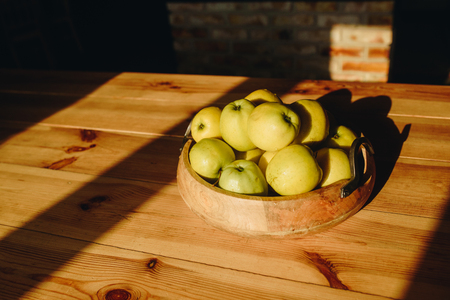 Healthy green food with apples on wood plates desk background mock up. Sunset time.