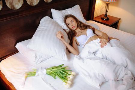 Foto de moda de jovencita sexy vistiendo ropa interior blanca, increíble cuerpo. Belleza en lencería. Atractiva joven novia en ropa interior acostada en la cama Foto de archivo - 84119830