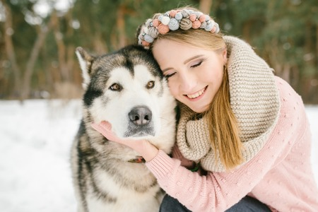 Walk with a friend. The girl hugs the dog and closes her eyes. Beauty and a dog in the winter forest. Close-up portrait. Stock Photo