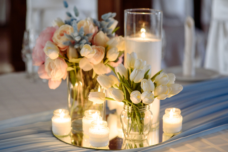 Wedding decorations. Fresh spring tulips and candles in glasses. Covered festive table. Bride idea. Stock Photo