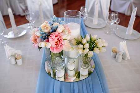 Wedding decorations. Fresh spring tulips and candles in glasses. Covered festive table. Bride idea. Stock Photo - 84730686