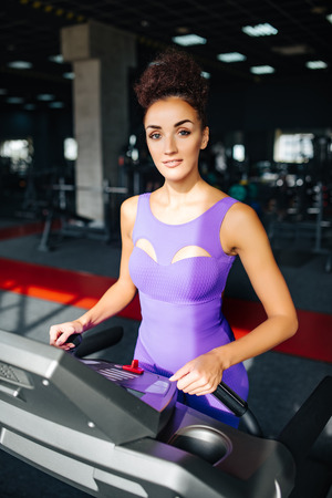 Sport world. Woman in violet sportswear running on a treadmill in front of window at gym. Jogging her way to good health. Stockfoto