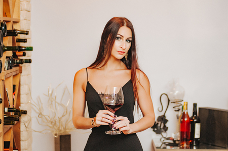 Sauvignon Portrait of a cute, charming, attractive, stylish female scientist in black dress, having raised a glass of red wine in his hand, to study a delicious drink.