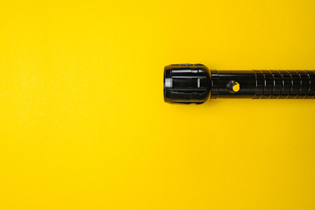 Travel and Search. Close-up of a flashlight on yellow background.