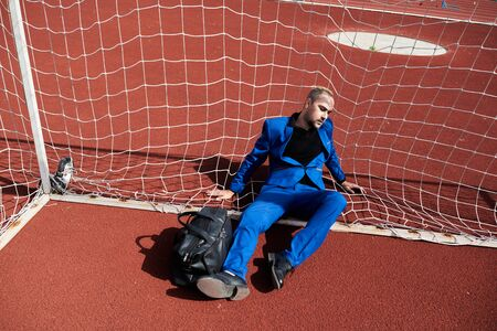 Business and quarantine. Man sitting in football gate on the track in the stadium.