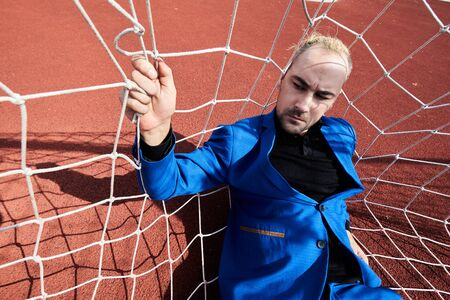 Alone and horror. Man in football net on the track in the stadium. Standard-Bild