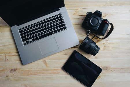 Photo journalism. Laptop, camera, tablet, note, camera lens.