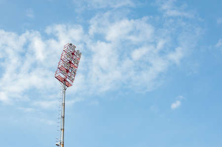 Floodlights with a metal pole for the sports arena. Tall high outdoor stadium spotlights on rigid frame construction with blue sky background