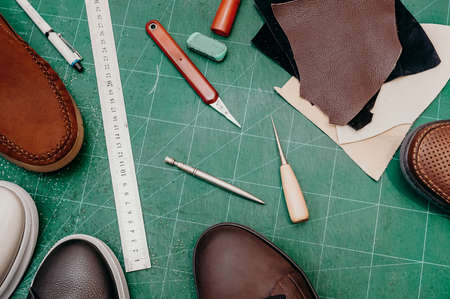 Tools for make of shoe. Ruler, awl, knife, paint and leather, shoe. Green background top view copy space Banco de Imagens