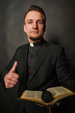 Priest man wearing catholic robe happy face smiling. Positive person.