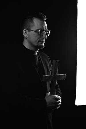 Mood religion. Priest man wearing catholic robe and glasses holding cross. Religion person.
