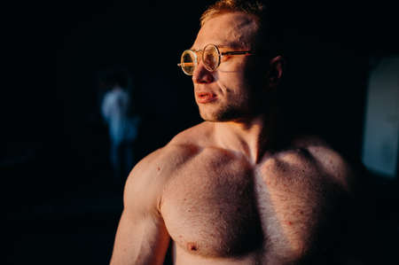 Muscular fitness shirtless man in glasses. Water drops on sport body.