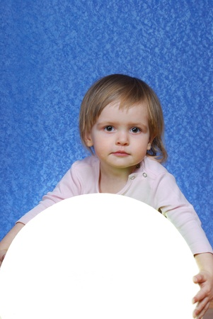 Child with ball, portrait on a blue background photo