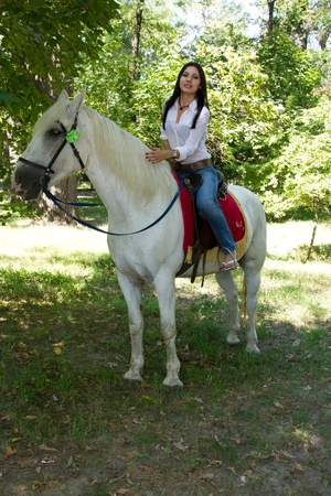 woman with black hair on a white horse  Stock Photo