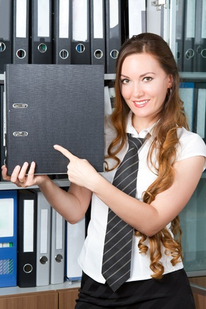 beautiful woman accountant points his finger at the folder in the office photo