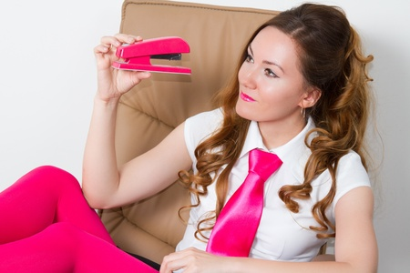 business woman in pink tights and tie looking at the  pink stapler in the office photo