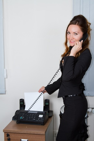 young businesswoman faxing document  photo