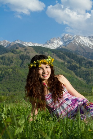 girl in wreaths of dandelions on the nature photo
