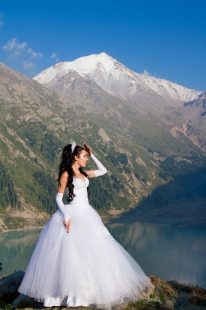 A married woman bride in her wedding dress in golden evening sunshine on a beautiful mountains in Kazakhstan