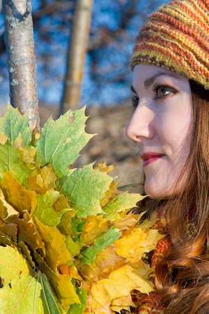 portrait of a beautiful woman in a yellow hat with leaves in autumn photo