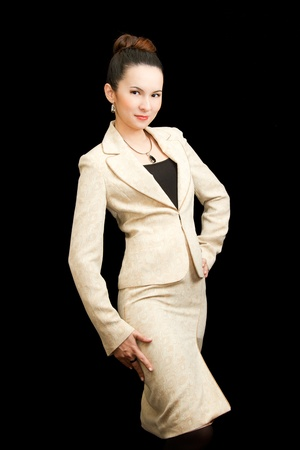 Asian businesswoman in a strict light-colored suit on a black background isolated.More of this series on my portfolio ! photo
