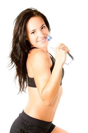 Woman drinking water from bottle after workout at gym on white isolated background. Stock Photo - 11312660