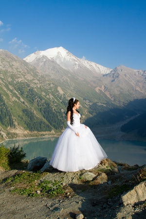 The sexy russian beautiful woman the bride in a wedding dress on mountain  photo