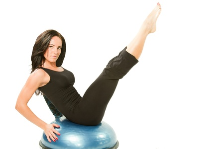 Portrait of healthy young woman practising yoga exercise on ball on isolated white background
