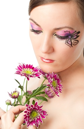 Pretty young woman with bodyart butterfly on face with  flower chrysanthemum isolated on white background photo