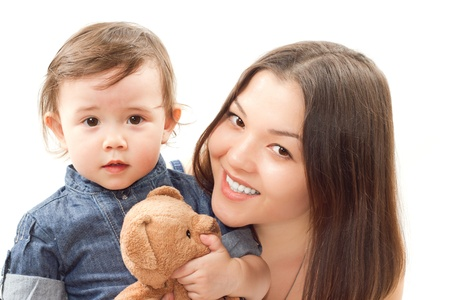 smiling mom and baby girl with toy bear on white background