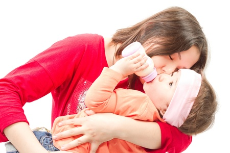 A mother kissing her smiling baby girl on the cheeks isolated on white background  photo
