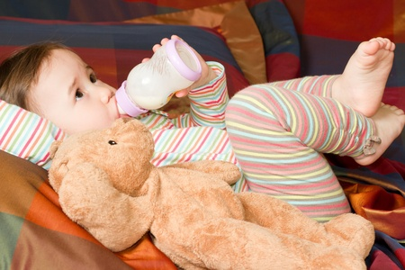 pretty baby girl with infant formula in bottle  on bad