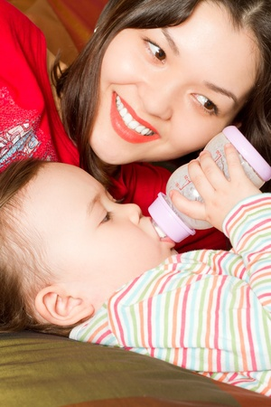mother feeds her baby with a bottle with infant formula in the house photo
