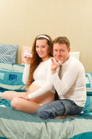 Portrait of a happy pregnant woman holding baby shoes and of her husband on sofa at home