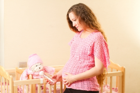 Pregnant woman with long hair feeding from a bottle with a nipple toy Teddy bear in a crib photo