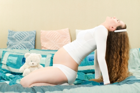 home birth: Pregnant woman with long hair in a yoga pose on sofa at home