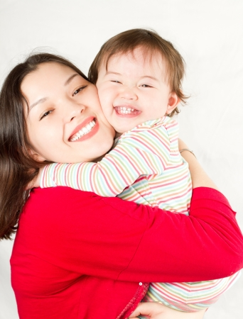 Happy mom and baby girl hugging and laughing