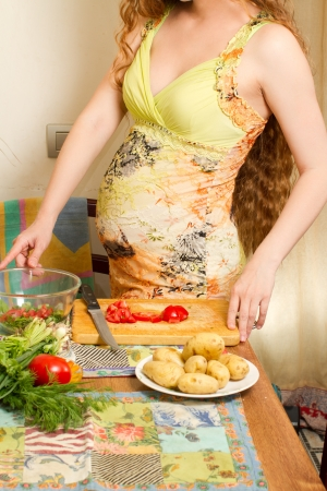 pregnant woman s hands and belly on kitchen with healthy food  The concept of food and a healthy lifestyle photo