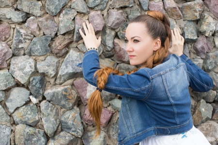 close up of portrait sexy  beautiful  woman in jeans jacket on stones  photo