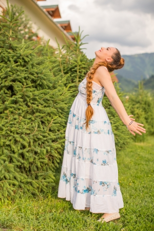 beautiful young pregnant woman with long hair resting on nature