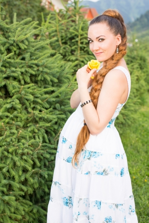 beautiful young pregnant woman with yellow flower rose  on nature photo