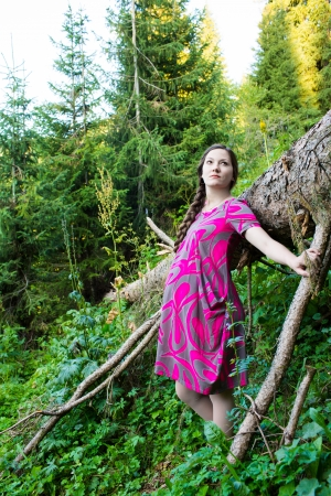 young pregnant woman near big tree in forest on nature photo