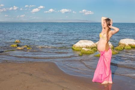 sexy pregnant woman: 水着ビーチでリラックス、健康の概念と残りの部分で幸せの美しい妊娠中の女性