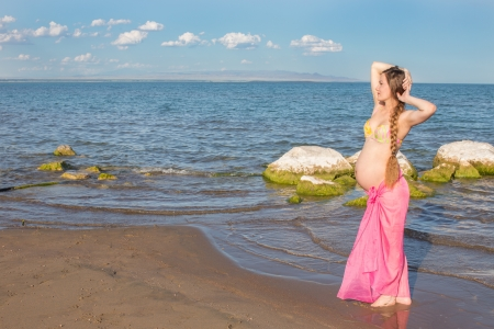 Happy beautiful pregnant woman in swimsuit  relaxing at beach  The concept of health and rest photo